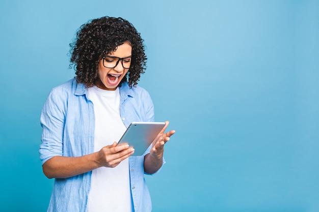 디지털 태블릿을 들고 텍스트, 로고 또는 광고 복사 공간이 격리 된 파란색 배경 위에 서 웃 고 곱슬 아프리카 머리를 가진 젊은 미국 학생 여자의 초상화.