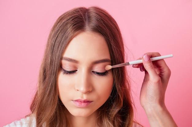 若くて魅力的な女の子とvisagisteメイクアップアーティストの肖像画は、ピンクの背景にスタジオで目にメイクを適用します。メイクアップスキンケアと美容のコンセプト。