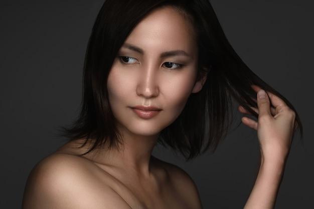 Портрет молодой и красивой азиатской женщины на серой стене