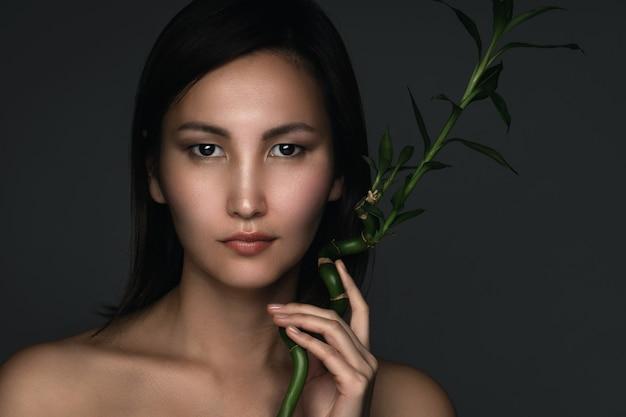 Портрет молодой и красивой азиатской женщины с бамбуковым растением в руках