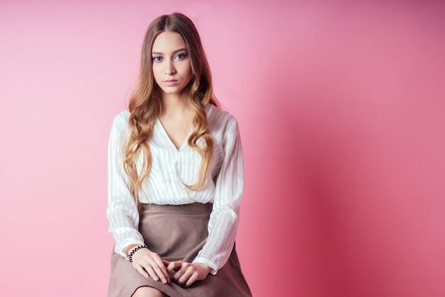 ピンクの背景にスタジオで若くて美しい女子高生女性ティーンエイジャーの肖像画