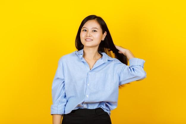 젊고 귀여운 중국, 일본 스타일 여성의 초상화는 노란색 카메라에 긍정적인 제스처와 친절한 미소로 카메라에 포즈를 취합니다.