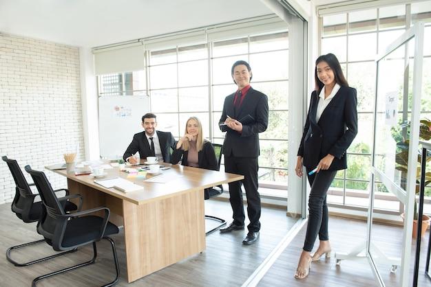 Портрет молодых и успешных кавказских и азиатских коллег в костюмах, встречающихся и смотрящих в камеру, стоя в рабочем пространстве