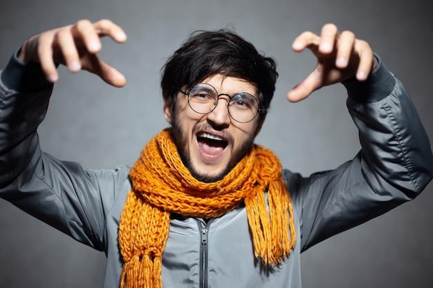 眼鏡とオレンジ色のスカーフを身に着けて、猫の爪のジェスチャーをしている若い怒っている男の肖像画