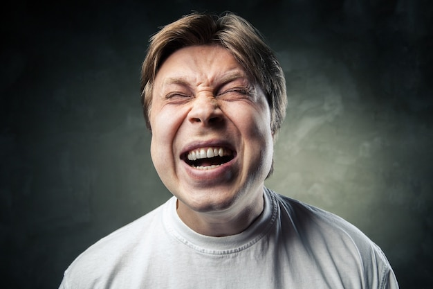 Портрет молодого сердитого человека на темно-сером фоне