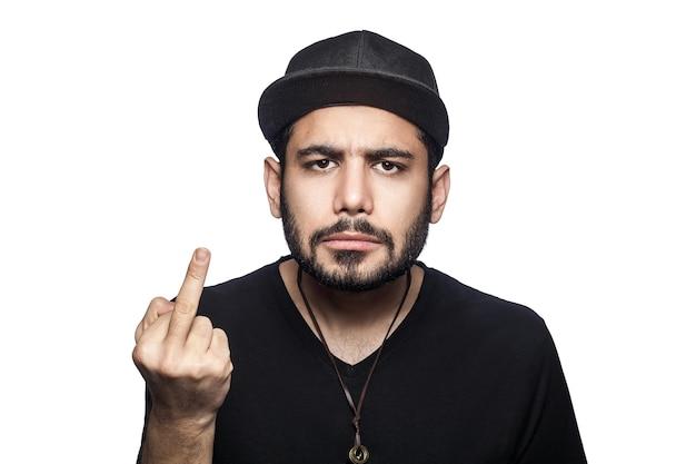카메라를 보고 가운데 손가락을 보여주는 검은 티셔츠와 모자를 쓴 젊은 화난 남자의 초상화. 스튜디오 촬영, 흰색 배경에 고립입니다.