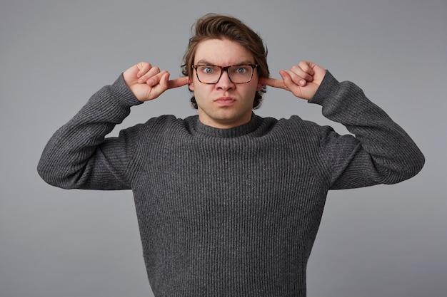 Портрет молодого сердитого человека в очках в сером свитере, стоит на сером фоне, не хочет слушать, обеспокоенный шумом, прикрывает уши пальцами.