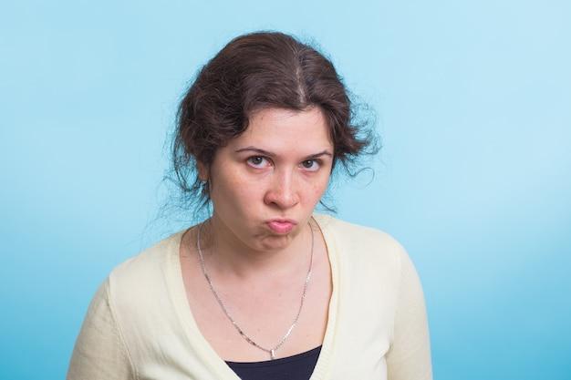 青い壁に怒っている若い女性の肖像画
