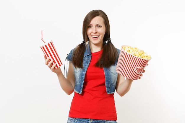 흰색 배경에 격리된 팝콘 양동이와 플라스틱 컵의 소다 또는 콜라를 들고 영화를 보는 캐주얼한 옷을 입은 젊은 성가신 매력적인 여성의 초상화. 영화 개념의 감정.