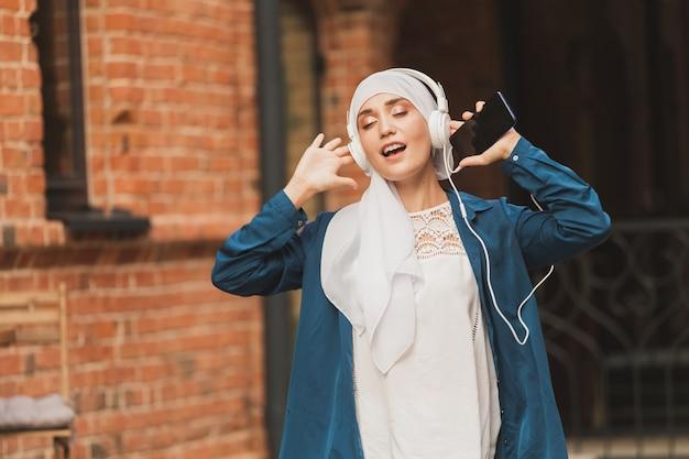헤드폰과 춤으로 음악을 듣고 있는 젊은 아라비아 이슬람 여성의 초상화. 페미니즘, 여성 독립, 여가 개념.