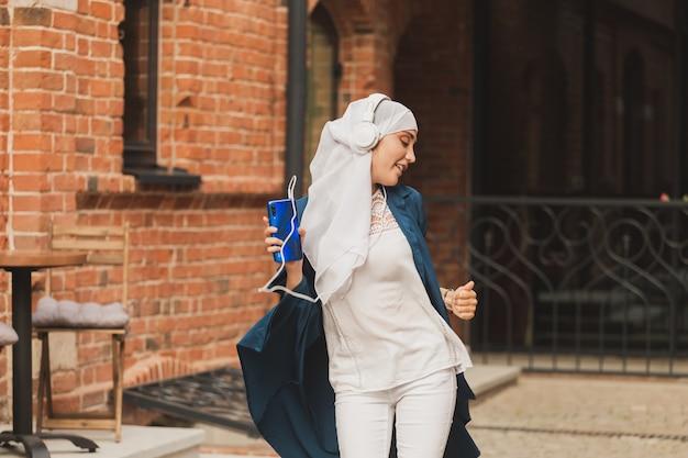 ヘッドフォンで音楽を聴き、フェミニズムの女性を踊る若いアラビアのイスラム教徒の女性の肖像画