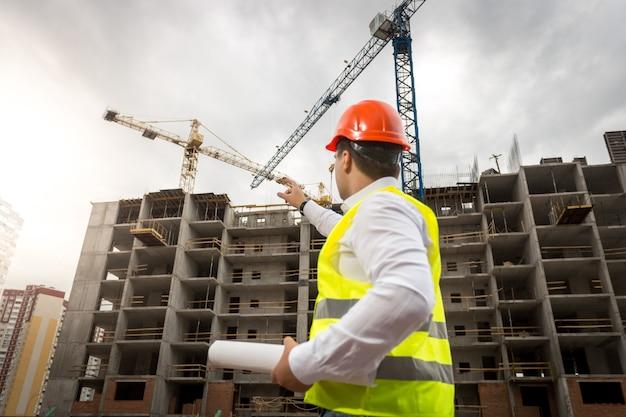 Портрет молодого архитектора, держащего чертежи и указывающего на строящееся здание