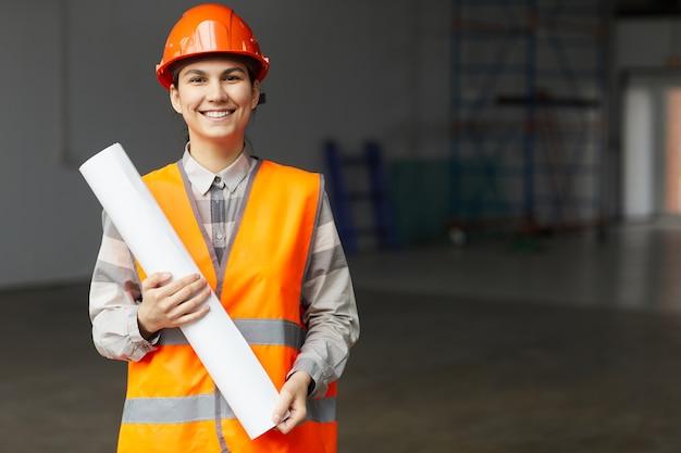 Портрет молодого архитектора в рабочем шлеме и светоотражающем жилете, держащего план и улыбающегося в камеру, стоя на строительной площадке