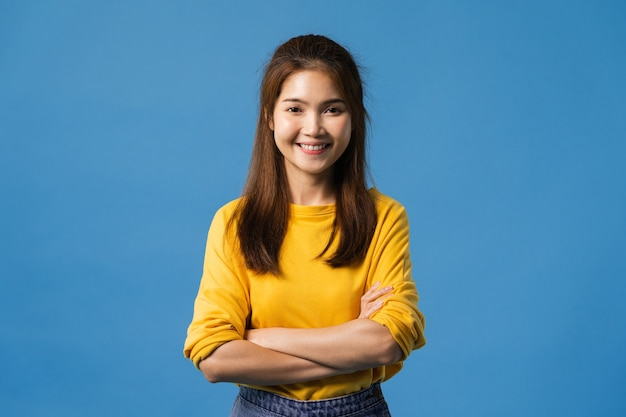 肯定的な表現、腕を組んで、広い笑顔、カジュアルな服を着て、青い背景の上にカメラを見て若いアジア女性の肖像画。幸せな愛らしい喜んで女性は成功を喜ぶ。