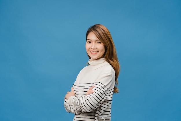 ポジティブな表情、腕を組んで、広く笑顔で、カジュアルな服を着て、青い壁の向こう側を見ている若いアジアの女性の肖像画