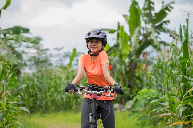 Портрет молодой азиатской красивой женщины, езда на велосипеде