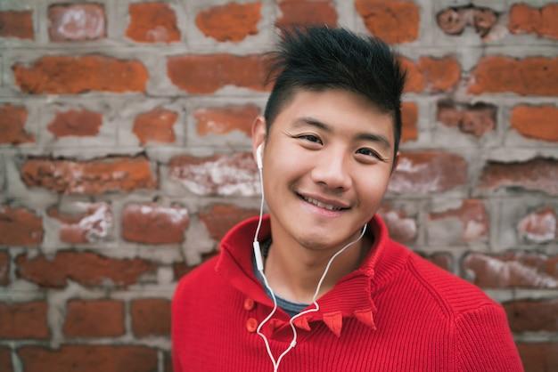 レンガの壁に屋外のイヤホンで音楽を聴く若いアジア少年の肖像画。都市のコンセプト。