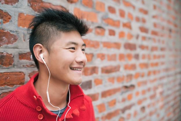 Портрет молодого азиатского мальчика, слушая музыку с наушниками на открытом воздухе против кирпичной стены. городская концепция.