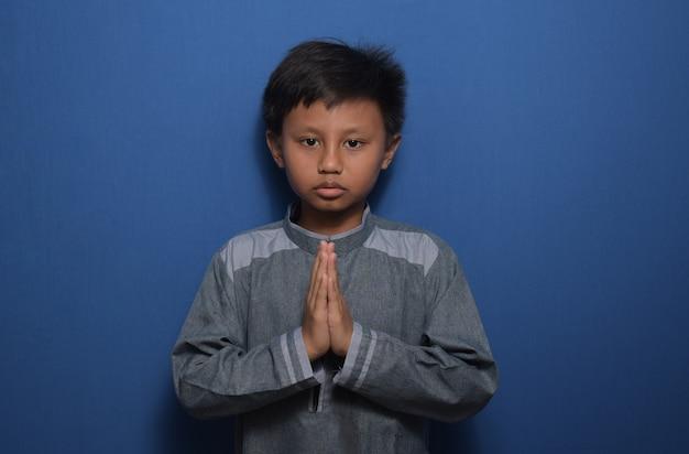 Портрет молодого азиатского мальчика в мусульманской одежде, положив ладони на грудь