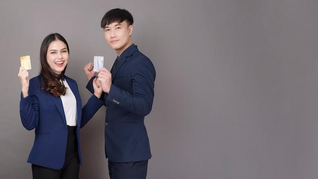 灰色のスタジオの背景にクレジットカードを持っている若いアジアビジネス人々の肖像画