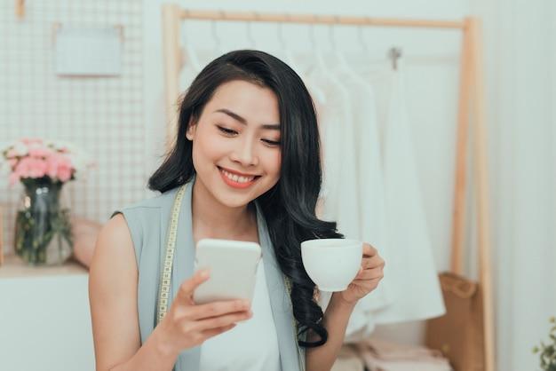 Портрет молодой азиатской деловой женщины / модельера отдыхают, пьют кофе и пользуются мобильным телефоном
