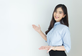 Portrait of young asian business woman presenting over white background.