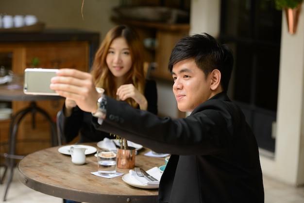 Портрет молодого азиатского бизнесмена и молодой азиатской коммерсантки, вместе расслабляющегося в кафе