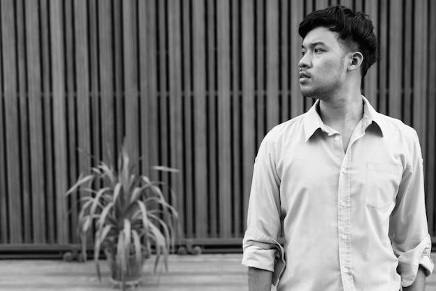 Портрет молодого азиатского бизнесмена на улицах против деревянных ворот на открытом воздухе