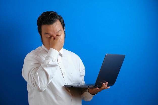 젊은 아시아 사업가의 초상화는 너무 오래 노트북 작업을 한 후 피곤해 보였고 머리가 뻣뻣해 보였다