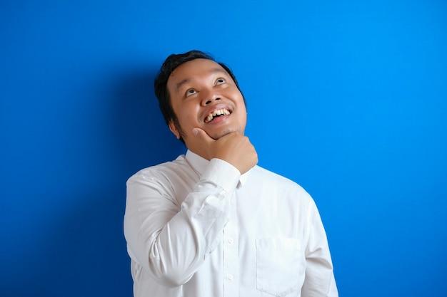 コピースペースと青い背景に対して、何かを考えて、良いアイデアを持って幸せに笑って、問題の解決策を見つける若いアジアのビジネスマンの肖像画