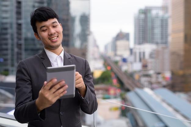 街の景色に対してデジタルタブレットを使用して若いアジアのビジネスマンの肖像画