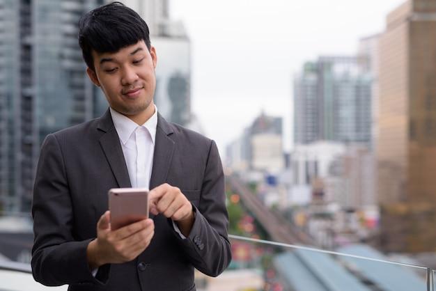 街の景色に対して電話を使用して若いアジアのビジネスマンの肖像画