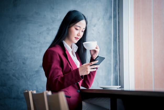 スマートフォンを使用してコーヒーを飲みながらカフェで室内に座っている若いアジア女性実業家の肖像画。ビジネスの成功の概念。