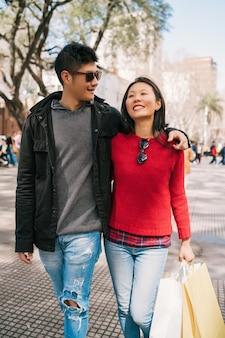 ショッピングの後に街を歩いている愛の若いアジアのカップルの肖像画。ショップコンセプト。