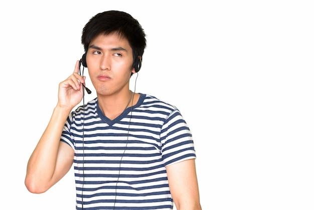 白い壁に隔離されたヘッドセットを身に着けている若いアジアの顧客サービス担当者の肖像画