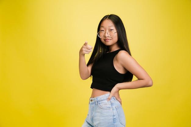 黄色のスタジオの背景に分離された若いアジアの女の子の肖像画
