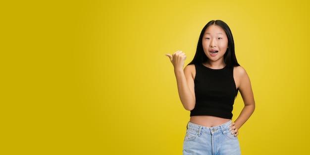 黄色のスタジオで隔離の若いアジアの女の子の肖像画