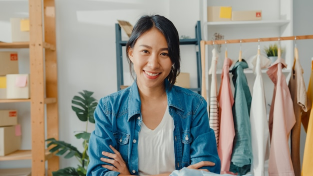 행복 한 미소로 젊은 아시아 여자 패션 디자이너의 초상화, 팔을 넘어 집에서 옷가게를 작업하는 동안 정면을보고