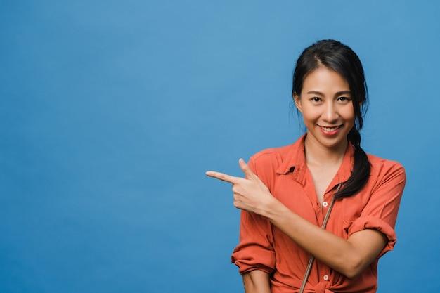 Портрет молодой азиатской леди, улыбающейся с веселым выражением лица, показывает что-то удивительное на пустом месте в повседневной ткани и смотрит в камеру, изолированную над синей стеной. концепция выражения лица.