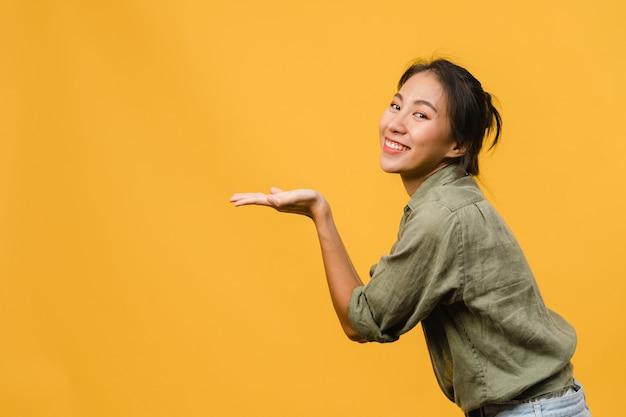 陽気な表情で笑っている若いアジアの女性の肖像画は、黄色の壁に隔離されたカジュアルな布の空白のスペースで素晴らしい何かを示しています。表情のコンセプト。