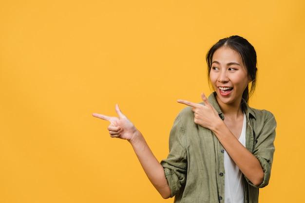 Портрет молодой азиатской леди, улыбающейся с веселым выражением лица, показывает что-то удивительное на пустом месте в повседневной одежде и стоящей изолированно над желтой стеной. концепция выражения лица.