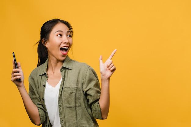 Портрет молодой азиатской леди, использующей мобильный телефон с веселым выражением лица, показывает что-то удивительное на пустом месте в повседневной одежде и стоит изолированно над желтой стеной. концепция выражения лица.