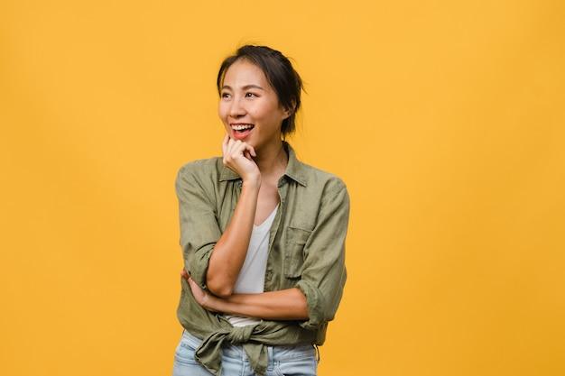 Портрет молодой азиатской леди с позитивным выражением лица, скрестив руки, широко улыбающейся, одетой в повседневную одежду над желтой стеной. счастливая очаровательная рада женщина радуется успеху. концепция выражения лица.