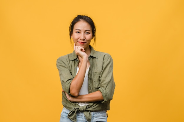 黄色の壁にカジュアルな服を着て、前向きな表情、腕を組んで、広く笑顔で、若いアジアの女性の肖像画。幸せな愛らしい嬉しい女性は成功を喜んでいます。