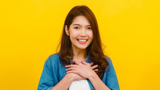 Портрет молодой азиатской леди с позитивным выражением, радостным и захватывающим, одетый в повседневную одежду и глядя на камеру через желтую стену. счастливая прелестная радостная женщина радуется успеху.