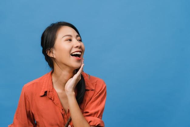 青い壁にカジュアルな服を着て、前向きな表情で、広く笑顔で、若いアジアの女性の肖像画。幸せな愛らしい嬉しい女性は成功を喜んでいます。表情のコンセプト。
