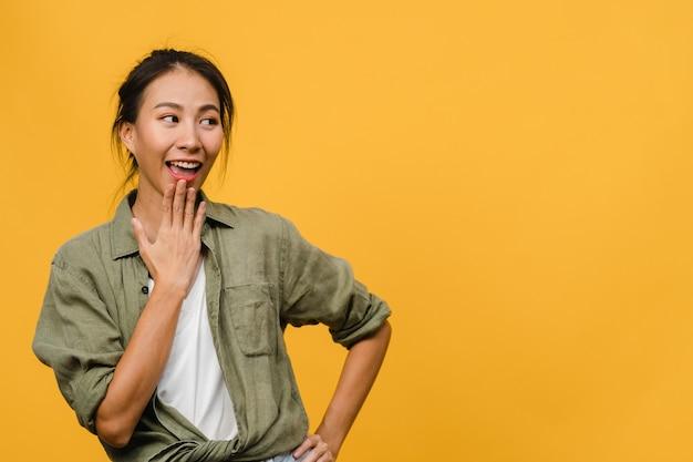 긍정적인 표정을 한 젊은 아시아 여성의 초상화는 노란 벽 위에 평상복을 입고 활짝 웃고 있습니다. 행복하고 사랑스러운 기쁜 여자는 성공을 기뻐합니다. 표정 개념입니다.