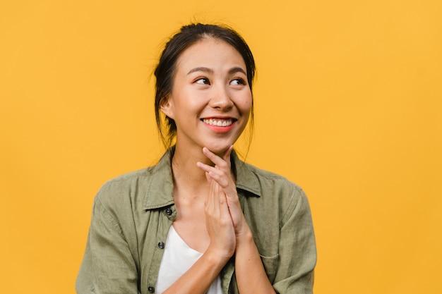 黄色の壁にカジュアルな服を着て、前向きな表情で、広く笑顔で、若いアジアの女性の肖像画。幸せな愛らしい嬉しい女性は成功を喜んでいます。表情のコンセプト。