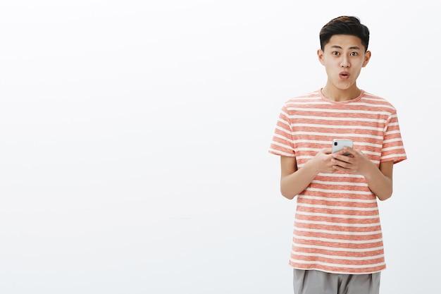 흰 벽에 접힌 입술로 와우라고 말하는 새로운 핸드폰 좋아하는 장치를 사용하여 흥분되는 스트라이프 티셔츠에 멋진 헤어 스타일을 가진 젊은 아시아 남성 청소년의 초상화