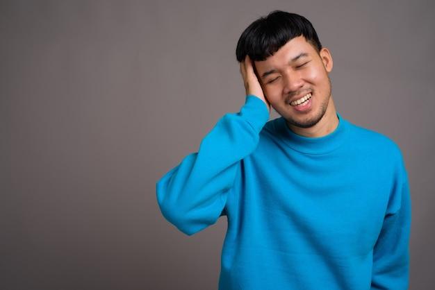 Портрет молодого азиатского человека против серого